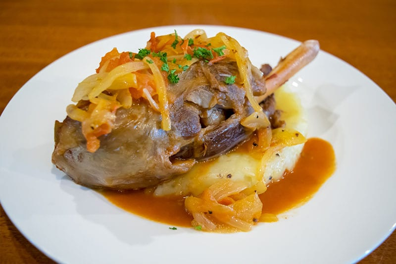 Slow cooked lamb shank in a tomato and onion broth with creamy mash